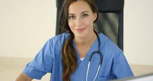 Le jeune médecin féminin place une main sur son visage Photographie stock