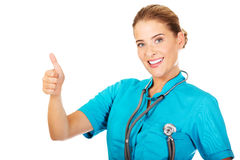 Le jeune médecin ou infirmière féminin avec le stethocope montre le pouce  images libres de droits