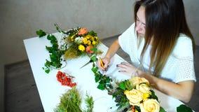 Le jeune manipulateur féminin de fleur garde le disque des fleurs et écrit o photographie stock