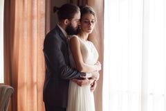 Le jeune marié étreint la jeune mariée de l'arrière, se tenant prêt la fenêtre Vue de côté images stock