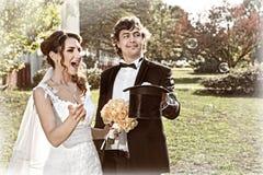 Le jeune marié créent des bulles à la jeune mariée du chapeau photo libre de droits