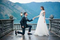 Le jeune marié propose le mariage sur un pont images stock