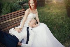 Le jeune marié se trouve sur la belle fille dans une robe de mariage en parc public sur le banc Photos stock