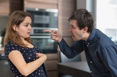 Le jeune mari de jalousie est criant et blâmant son épouse images stock