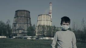 Le jeune masque de port de pollution saisit sa tête et regrets Type restant contre des cheminées d'usine banque de vidéos