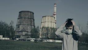 Le jeune masque de port de pollution saisit sa tête et regrets Type restant contre des cheminées d'usine clips vidéos