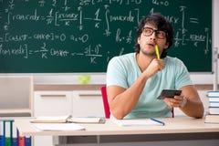 Le jeune mathématicien d'étudiant masculin devant le tableau photo libre de droits