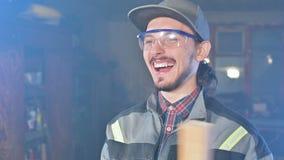 Le jeune menuisier barbu concentré dans les lunettes et un chapeau examine l'objet pour assurer l'aptitude tout en la tenant dans banque de vidéos