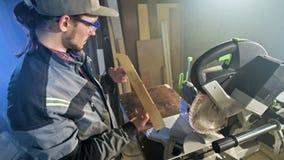 Le jeune menuisier barbu concentré dans les lunettes et un chapeau examine l'objet pour assurer l'aptitude tout en la tenant dans clips vidéos