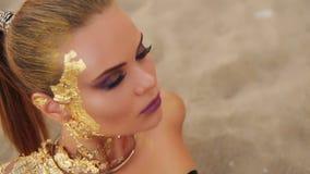 Le jeune modèle avec le maquillage d'or professionnel d'art dans le maillot de bain en cuir noir s'étendant sur la plage regarde  banque de vidéos