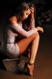 Le jeune modèle dans la robe et des chaussures de guipure se repose sur une roche Pieds dans l'eau sous la pluie Image libre de droits