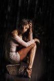 Le jeune modèle dans la robe et des chaussures de guipure se repose sur une roche Pieds dans l'eau sous la pluie Photos libres de droits