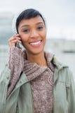 Le jeune modèle joyeux en hiver vêtx donner un appel téléphonique Photographie stock libre de droits