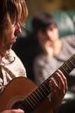 Le jeune musicien joue sa guitare pendant que l'ami écoute Image stock