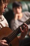 Le jeune musicien joue sa guitare pendant que l'ami écoute Photo libre de droits