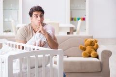 Le jeune père appréciant le temps avec le bébé nouveau-né à la maison Photos stock