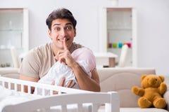 Le jeune père appréciant le temps avec le bébé nouveau-né à la maison Image libre de droits