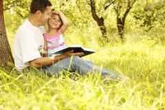 Le jeune père avec sa petite fille lit la bible image libre de droits