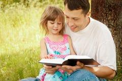 Le jeune père avec sa petite fille lit la bible images libres de droits