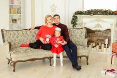 Le jeune père et la mère enceinte s'asseyant avec la petite fille sur le sofa près ont décoré la cheminée photo stock