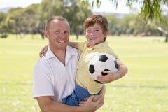 Le jeune père heureux continuant le sien de retour a excité 7 ou 8 années de fils jouant ensemble le football du football sur le  Photo libre de droits
