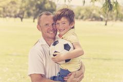 Le jeune père heureux continuant le sien de retour a excité 7 ou 8 années de fils jouant ensemble le football du football sur le  Photos stock