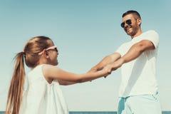 Le jeune père heureux dans des lunettes de soleil tourne avec la fille, tenant des mains images libres de droits