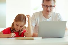Le jeune père heureux ont l'amusement avec sa jolie fille pendant le travail images stock