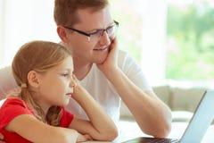 Le jeune père heureux ont l'amusement avec sa jolie fille pendant le travail image libre de droits