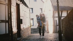 Le jeune père tient deux enfants heureux dans des ses bras Homme européen bel avec le garçon et les mains et le sourire de ondula clips vidéos
