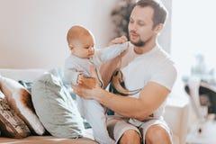Le jeune père tient son soleil minuscule sur le sofa dans la salle légère photographie stock libre de droits