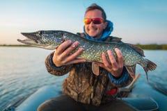 Le jeune pêcheur à la ligne heureux tient les poissons de brochet Image libre de droits