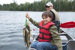 Le jeune pêcheur tient fièrement la lisse des brochets vairons Photos stock