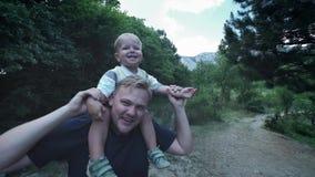 Le jeune p?re heureux tient son tour de ferroutage de fils sur ses ?paules et rechercher Le petit gar?on s'assied sur le dos dess clips vidéos