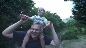 Le jeune p?re heureux tient son tour de ferroutage de fils sur ses ?paules et rechercher Le petit gar?on s'assied sur le dos dess banque de vidéos