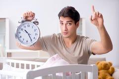 Le jeune papa avec l'horloge près du berceau nouveau-né de lit de bébé image stock