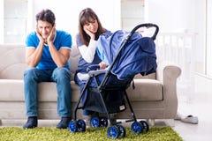 Le jeune parents avec leur bébé nouveau-né dans le landau de bébé se reposant sur le sofa images stock
