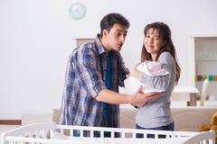 Le jeune parents avec leur bébé nouveau-né près du berceau de lit photos libres de droits
