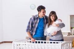 Le jeune parents avec leur bébé nouveau-né près du berceau de lit photo stock