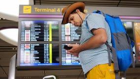 Le jeune passager de touristes beau d'aéroport international dans le chapeau emploie des supports de téléphone portable avec le s Photographie stock