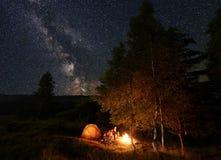 Le jeune peson par le feu de camp se reposant sur des rondins pendant le camping de nuit parmi des arbres s'approchent de la tent Image libre de droits