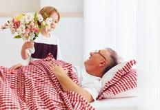 Le jeune petit-fils avec le bouquet de fleur est venu chez son grand-papa malade dans la salle d'hôpital Images stock