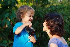 Le jeune photographe de sourire tire sa mère Photos stock