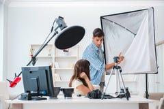 Le jeune photographe travaillant dans le studio de photo Images stock
