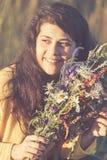 Le jeune portrait de sourire mignon de fille avec le champ fleurit pendant le coucher du soleil d'été Image modifiée la tonalité photos stock