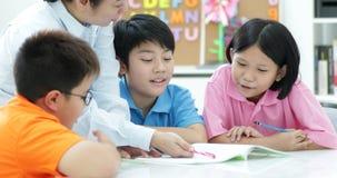 Le jeune professeur asiatique aide de jeunes enfants d'école dans la classe, banque de vidéos