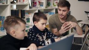 Le jeune professeur masculin attarctive de programmeur explique quelque chose au sujet des technologies et des ordinateurs à ses  banque de vidéos