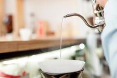 Le jeune propriétaire qualifié de café fait le café photographie stock libre de droits