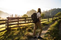 Le jeune randonneur féminin fait la manière entrant vers le haut dans la belle zone rurale de montagnes carpathiennes en Ukraine Images stock