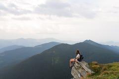 Le jeune randonneur féminin s'assied sur la roche dans le secteur de montagne magnifique et regarde dans l'horizon sans fin Photos libres de droits